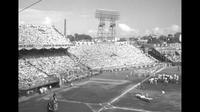 pan crowds in stands at stadium / cu spectators watch game / pan crowds in stands and band marching onto field / vs bands and teams marching onto... - general macarthur stock videos and b-roll footage