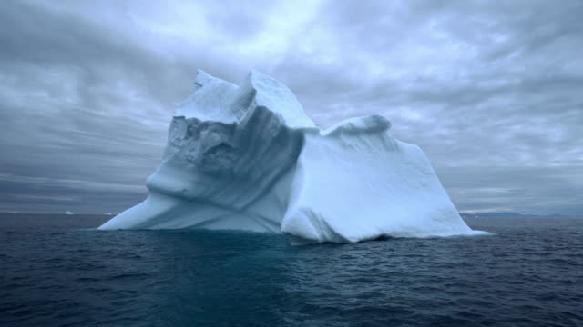pan: dark waves lap at the base of a magnificent iceberg after dusk on disko bay - headquarters stock videos & royalty-free footage