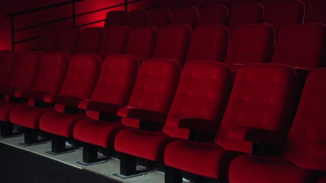 pan dolly shot through empty theater with red seats - biosalong bildbanksvideor och videomaterial från bakom kulisserna