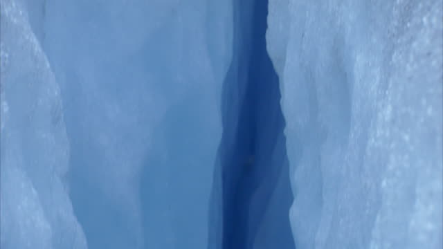 Pan down a deep blue crevasse in the ice of Nigardsbreen glacier