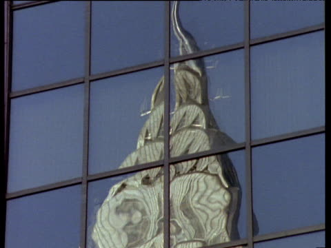 vídeos de stock e filmes b-roll de pan down a reflection of the chrysler building in the windows of another skyscraper in new york city. - prédio chrysler