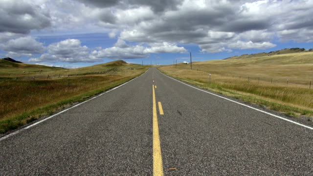 pan down and up of wide angle view of empty paved road with puffy clouds and blue sky with shadows rolling across landscape. - 30 seconds or greater stock videos & royalty-free footage