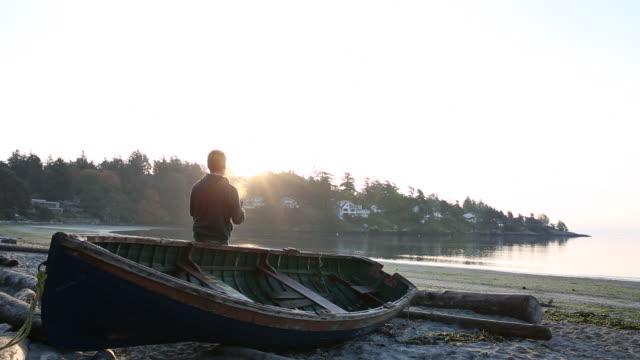 pan down as man uses digital tablet at sunrise by boat and ocean - カナダ ビクトリア市点の映像素材/bロール