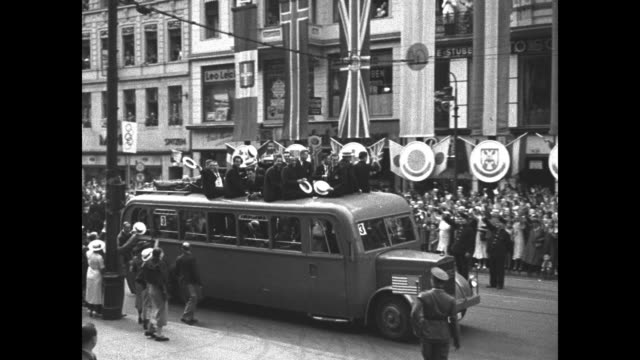 vídeos y material grabado en eventos de stock de pan down ext berlin city hall to nazi banners hanging along street below with crowds watching as traffic passes / crowds line street as bus carrying... - rathaus