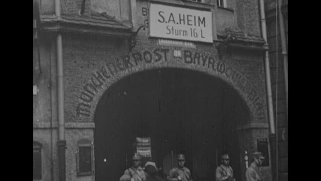 pan down ext building in munich with sa troops standing guard / vs armed sa troops in streets - nazi brown shirts stock videos & royalty-free footage