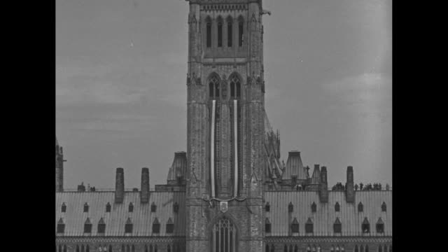 pan down ext peace tower of centre block in ottawa to crowds and ceremony held in observance of george vi's coronation / ws ceremony with crowds /... - ottawa stock videos & royalty-free footage