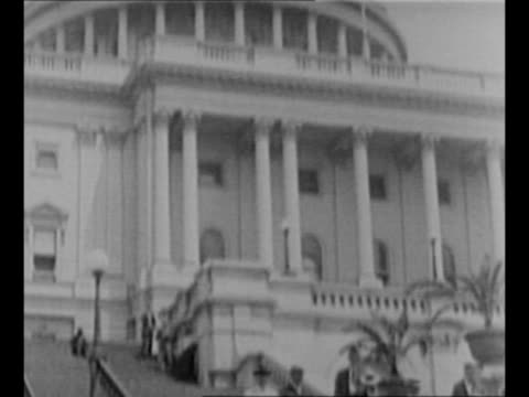 stockvideo's en b-roll-footage met pan down ext us capitol dome to group of us senators walking down capitol steps including warren g harding / ms the senators / harding and wife... - 1921