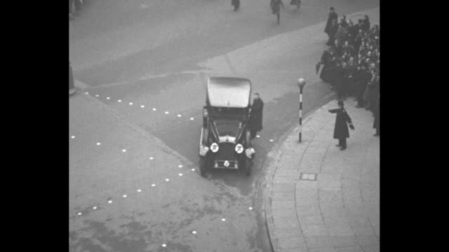 pan down exterior of bbc broadcasting house / crowd gathered on sidewalk / edward viii's car arrives at bbc as crowd closes in with policemen holding... - bbc stock videos & royalty-free footage