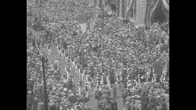 pan down exterior of the holy name cathedral to large crowd in front and american flags hanging above / pan packed crowd / vs police line holds back... - 1926 stock videos & royalty-free footage