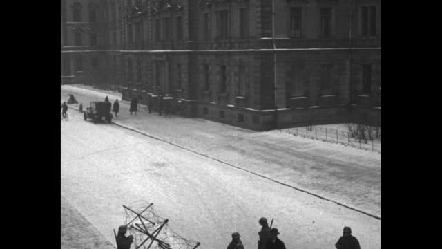 vidéos et rushes de pan down from a municipal building to a snowy street with german soldiers and barbed wire barricades / the soldiers check identification papers of... - armée allemande