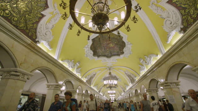 pan down from chandelier in moscow's underground metro to commuters. - metropolitana video stock e b–roll