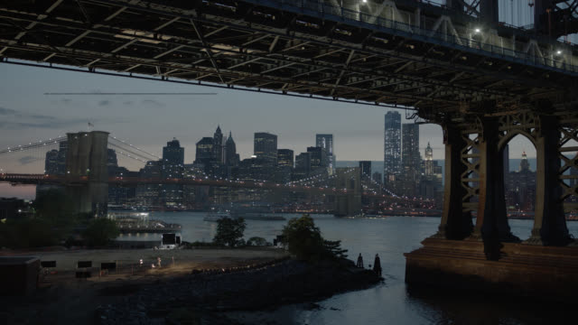 pan down from manhattan bridge and new york city skyline to city street under bridge. brooklyn bridge and east river visible. boats and cargo ship visible in river. - richtung stock-videos und b-roll-filmmaterial