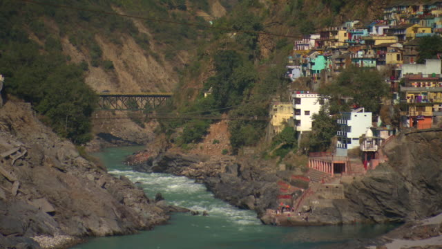 Pan down from mountains to the Ganges flowing past the town of Devprayag.