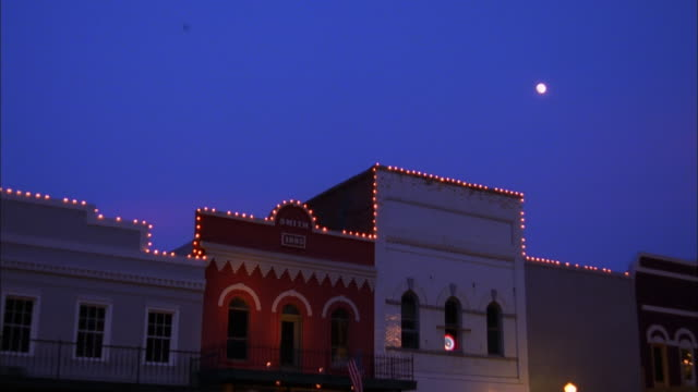 Pan down from night sky to illuminated building facades with balconies, Canton, Mississippi Available in HD.