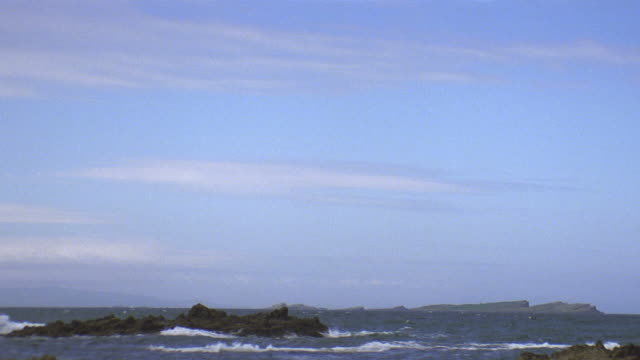 pan down from sky to rocky shoreline - horizon over water stock videos & royalty-free footage