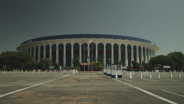 pan down from sky to the forum stadium. parking lot empty. - inglewood video stock e b–roll