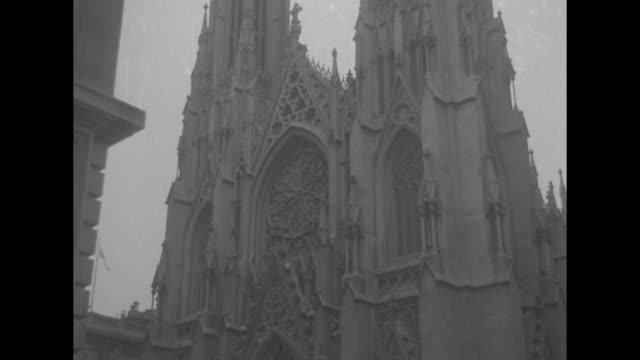 pan down from spires of st patrick's cathedral to people on the street with doubledecker buses - st. patrick's cathedral manhattan stock videos and b-roll footage