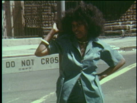 vidéos et rushes de pan down from street sign - edgecombe ave and w 136th st - to woman leaning against the pole. - coiffure afro