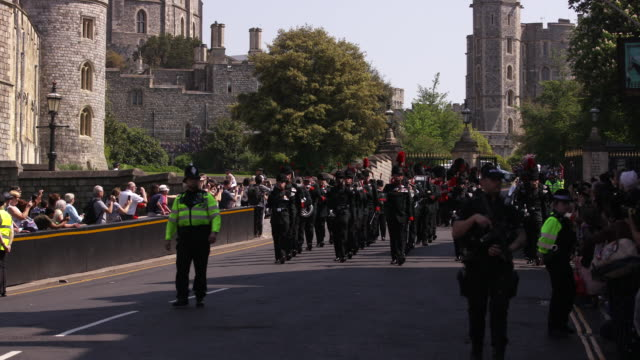 pan down from the queen victoria statue to a military band marching past windsor castle in windsor, england. - music or celebrities or fashion or film industry or film premiere or youth culture or novelty item or vacations stock videos & royalty-free footage