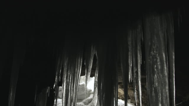 Pan down icicles hanging from the ceiling of a cave.
