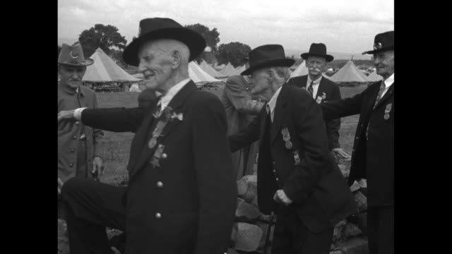 vídeos de stock, filmes e b-roll de pan down line of union army and confederate army veterans shaking hands over stone wall that marks the spot of battle in gettysburg national... - exército da união
