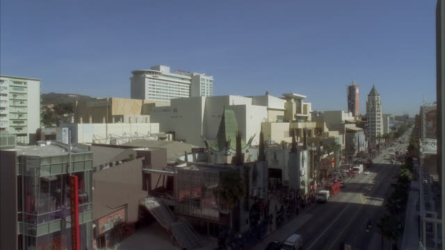 pan down of hollywood boulevard. movie theaters, multi-story and high rise office or apartment buildings. crowds of people, pedestrians, tourists. landmarks. cars on city street. hollywood walk of fame. los angeles area. - walk of fame stock-videos und b-roll-filmmaterial
