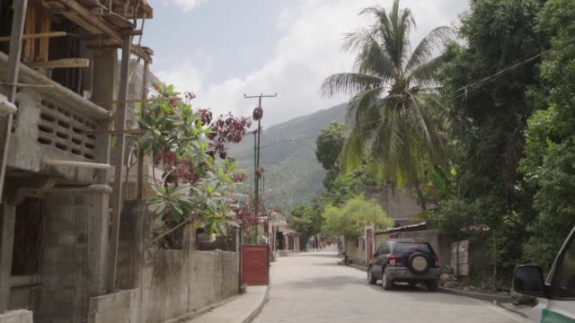 a pan down of tropical street with green hills in background - haiti stock videos & royalty-free footage