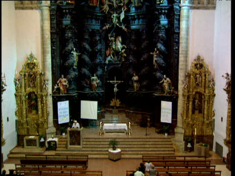 stockvideo's en b-roll-footage met pan down over catholic church from ornate backdrop to worshippers basque country spain - gelovige