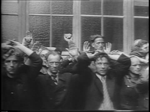 pan down row of german soldiers and collaborators on street with hands on their heads / montage of close-ups on captured soldiers' faces. - ゲシュタポ点の映像素材/bロール