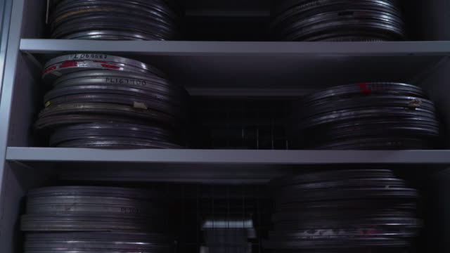 stockvideo's en b-roll-footage met pan down shelving units holding stacks of metal film cans - klos