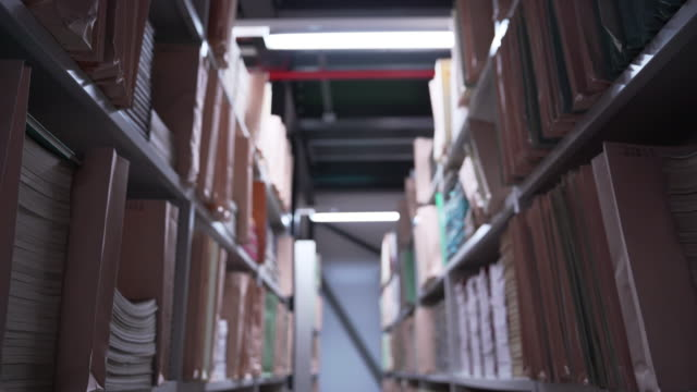 pan down shot between two shelving units containing paper manuscripts - file stock videos & royalty-free footage