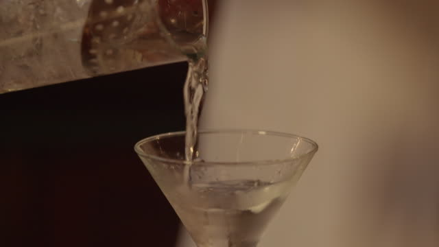 pan down shot of a bartender pouring a cocktail into a cocktail glass - martini stock videos & royalty-free footage