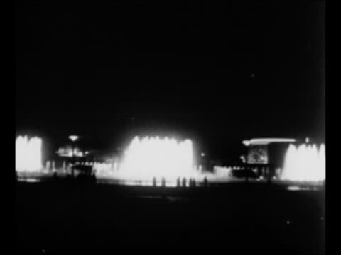 pan down statue of george washington on the grounds of the 1939 new york world's fair / night illuminated fountain flows as pedestrians pass in front... - world's fair stock videos and b-roll footage