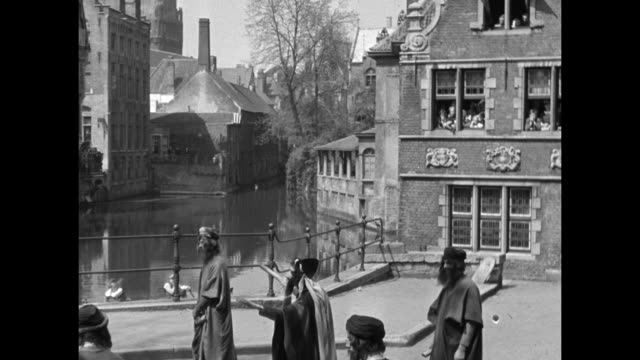 pan down steeples and buildings to pond and men dressed in medieval garb performing on pavement during may day celebration in brussels / prince... - pavement点の映像素材/bロール