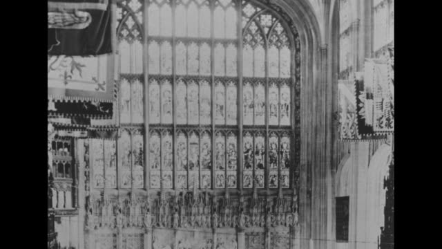 pan down still int st george's chapel at windsor castle from stained glass window to funeral service for king george vi with rear view queen... - stained clothes stock videos and b-roll footage