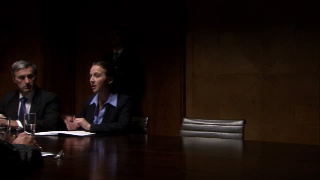 MS pan down table in dark room as five businesspeople have board meeting/ London