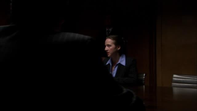 vidéos et rushes de ms pan down table in dark room as five businesspeople have board meeting/ london  - salle de réunion