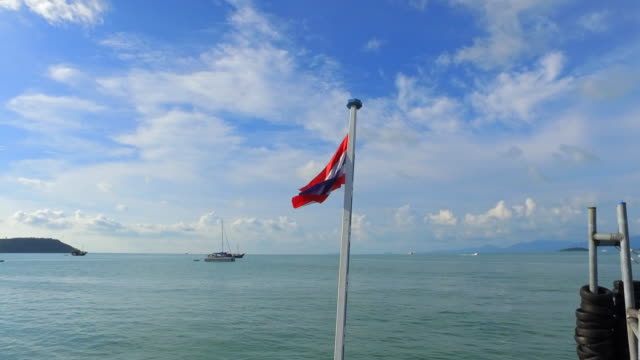pan down: thailand flag on post in ocean blowing in breeze - ko samui, thailand - ko samui stock videos and b-roll footage