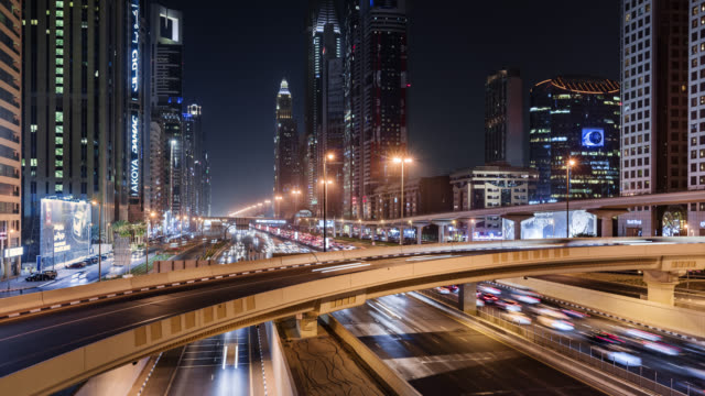 tl/pd pan down time lapse of sheikh zayed road , busy with commuting traffic at night, situated in dubai's financial district - electricity stock videos & royalty-free footage