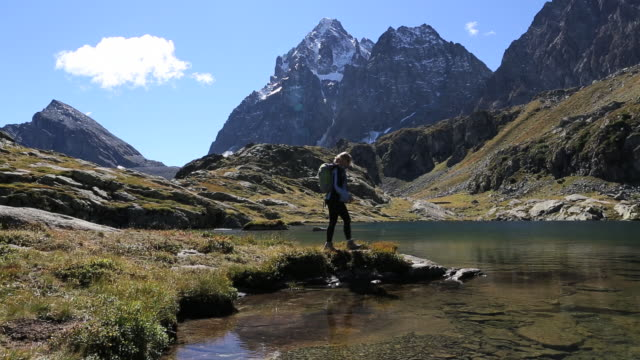 pan down to hiker arriving at mtn lake, takes picture - one mid adult woman only stock videos & royalty-free footage