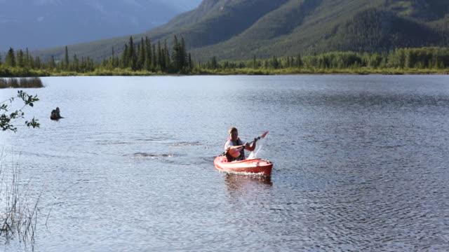pan down to kayaker approaching dock edge, mtn lake - kayaking stock videos & royalty-free footage