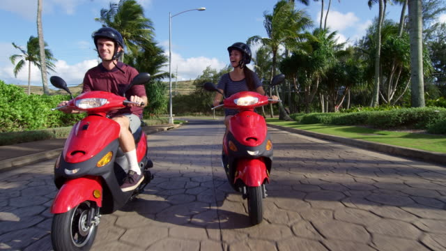 Pan down to show a couple having fun while riding mopeds