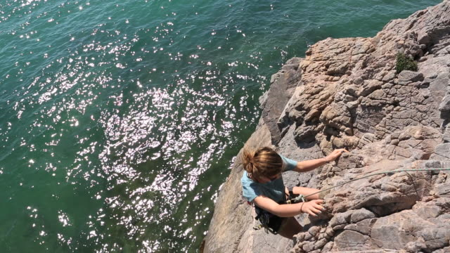 pan down to teen  girl being lowered on climbing rope, sea - one teenage girl only stock videos & royalty-free footage