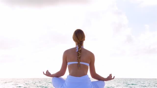 vídeos de stock, filmes e b-roll de ms pan down, young woman doing yoga at tropical beach - toalha de praia