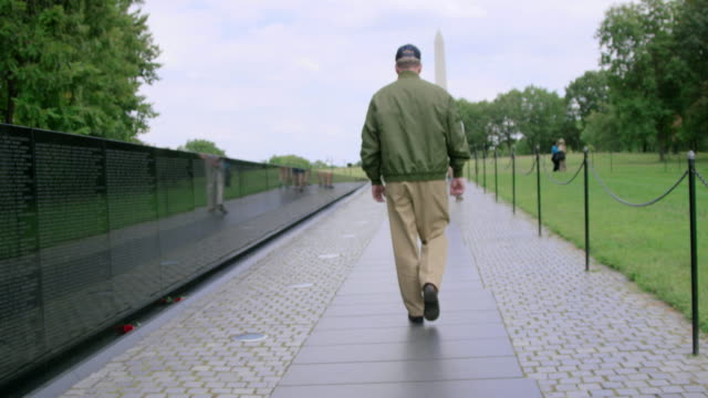 pan downward: veteran walking down the memorial (shot on red) - 退役軍人点の映像素材/bロール