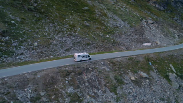 pan: drone footage of van on road along mountain - geiranger fjord, norway - 沿岸点の映像素材/bロール