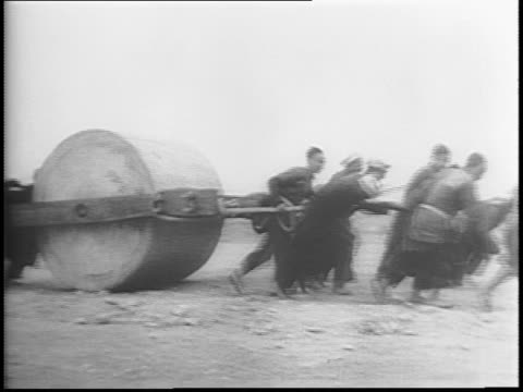 Pan expanse of air field with peasant laborers hoeing and digging / hundreds of laborers pull huge primitive roller to level surface / B29 Air...