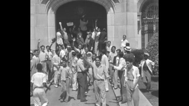 vídeos de stock, filmes e b-roll de pan exterior of machado palace as mob trashes and loots it / mob stands at front door of palace waving arm, cheering, jumping around / signs on... - multidão violenta