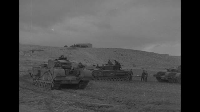 pan flat desert and mud, probably in algeria, with military vehicle approaching on makeshift board bridge; soldiers ride atop / tank with allied... - kampfpanzer stock-videos und b-roll-filmmaterial