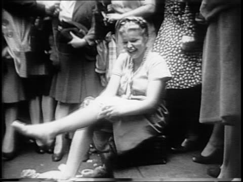 pan following woman's legs walking, handwritten sign in window, 'nylons on sale!', montage of crowds gather outside stores, police directing crowd,... - stockings stock videos & royalty-free footage